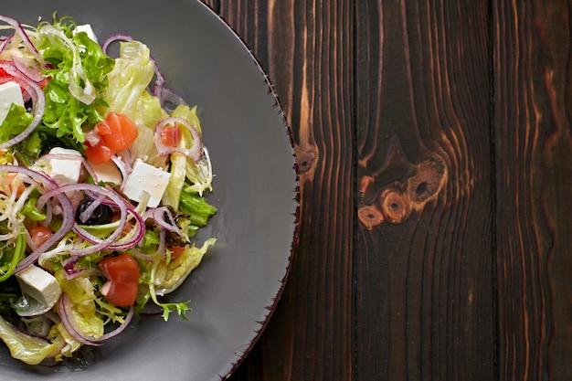 Салатный микс с лососем, сыром фета, луком и оливками, на тарелке, на деревянной поверхности