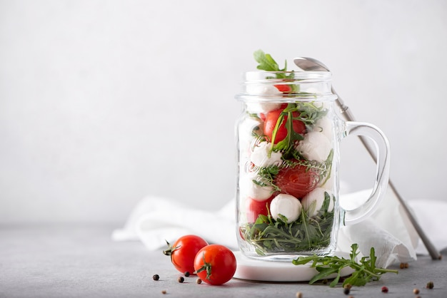 Salad of mozzarella, cherry tomatoes and arugula in a glass mug, on a light background
