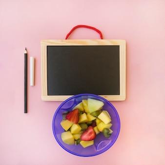 Salad near pencil and chalkboard