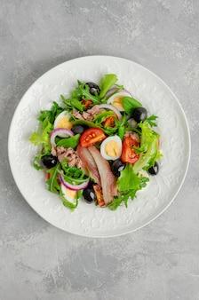 Салат нисуаз с тунцом, яйцом, стручковой фасолью, помидорами, оливками, листьями салата, луком и анчоусами