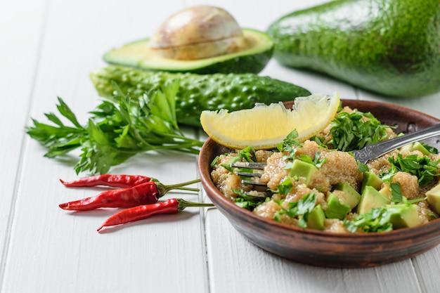 白い木製のテーブルにオリーブオイルとアマランス、アボカド、コショウ、レモン、パセリの種子のサラダ。