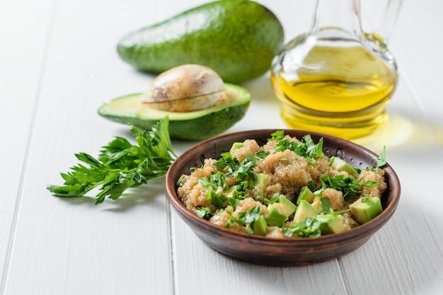 白い木製のテーブルにオリーブオイルとアマランスの種子、アボカド、パセリのサラダ。