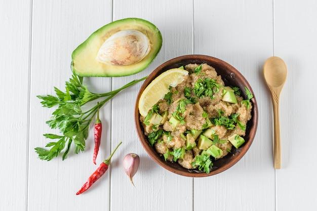 アマランスの種子、アボカド、唐辛子、トマト、レモン、パセリのオリーブオイルと白い素朴なテーブルに木のスプーンのサラダ。上からの眺め。