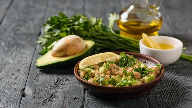 アマランスの種子、アボカド、レモン、パセリのオリーブオイルとグレーのテーブルに半分のアボカコのサラダ。