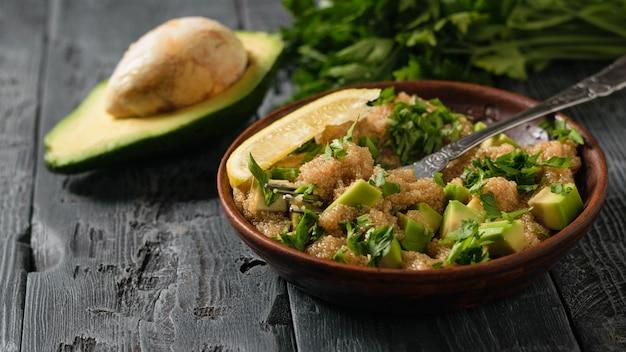 アマランスの種、アボカド、レモン、パセリのサラダ、素朴なテーブルにオリーブオイルと半分のアボカコ。