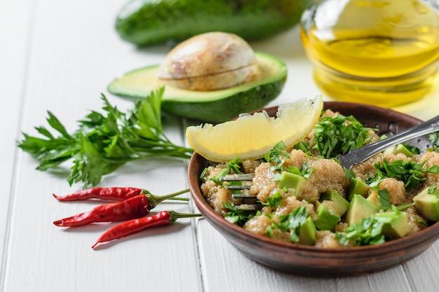 白いテーブルにオリーブオイルとアマランスの種子、アボカド、コショウ、レモン、パセリのサラダ。