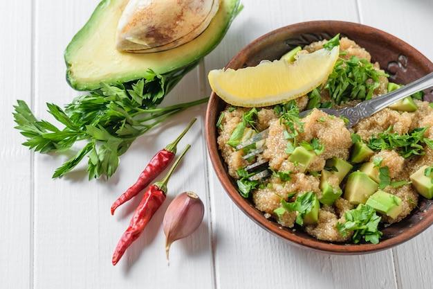 白い木製のテーブルにオリーブオイルとアマランスの種子、アボカド、コショウ、レモン、パセリのサラダ。上からの眺め。