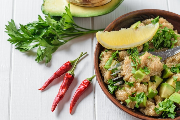 アマランスの種子、アボカド、コショウ、トマト、レモン、パセリのサラダ、白いライトテーブルにオリーブオイル。上からの眺め。