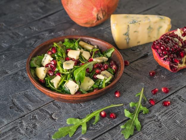 Arugula, 석류 및 어두운 나무 테이블에 파란색 곰팡이와 치즈 샐러드. 다이어트 채식 샐러드.