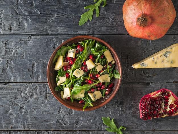 Arugula, 석류 및 소박한 테이블에 파란색 곰팡이와 치즈 샐러드. 다이어트 채식 샐러드. 평평하다.