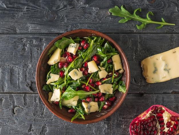 Arugula, 석류, 나무 테이블에 파란색 곰팡이와 치즈 샐러드. 다이어트 채식 샐러드. 평평하다.