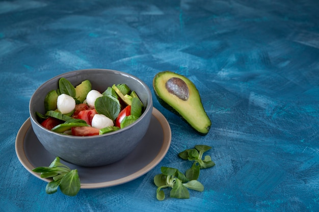 Салат из авокадо, моцареллы, помидоров, базилика на фоне стола