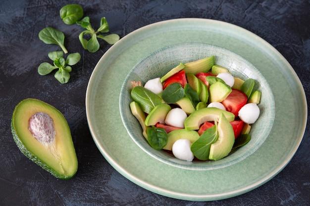 Салат из авокадо, помидоров, моцареллы, базилика на фоне стола
