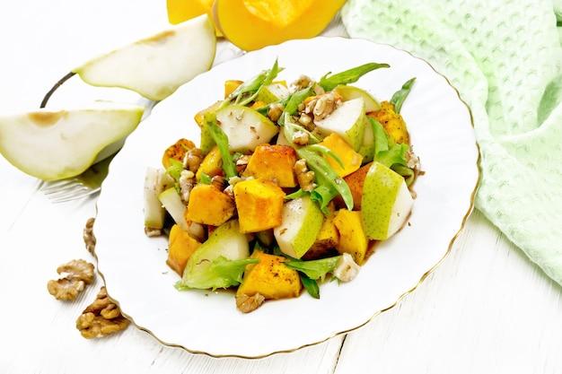 Салат из запеченной тыквы, свежей груши, рукколы и грецких орехов, заправленный медом, бальзамическим уксусом, специями и растительным маслом в тарелке.