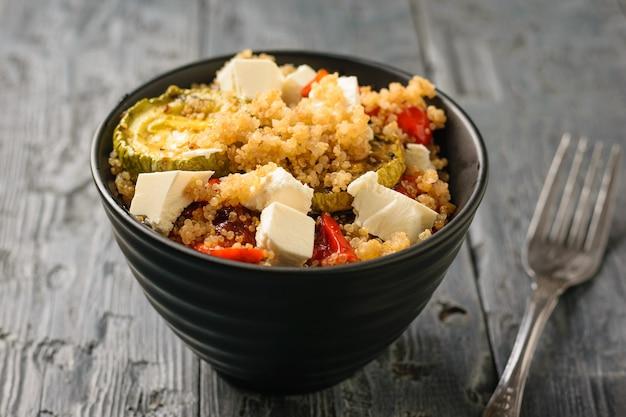 Салат из отварной крупы киноа, овощей и кусочков сербского сыра. вегетарианское блюдо. натуральная растительная пища. вид сверху.