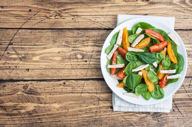 イカの煮物、フレッシュトマト、ほうれん草の葉のサラダ。野菜とシーフードが入ったおいしい明るいダイエット料理。スペース上面図をコピー