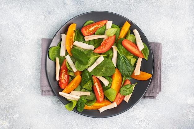 イカの煮物、フレッシュトマト、ほうれん草の葉のサラダ。野菜とシーフードが入ったおいしい明るいダイエット料理。コピースペース。上面図