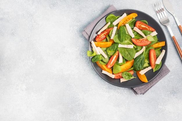 삶은 오징어, 신선한 토마토, 시금치 잎 샐러드. 야채와 해산물로 맛있는 밝은 다이어트 요리. 복사 공간. 평면도