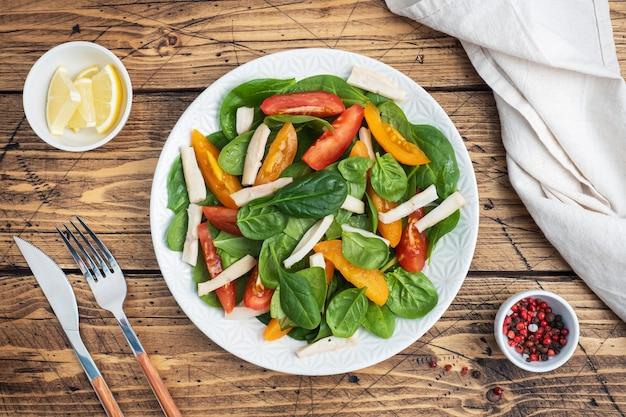 삶은 오징어 샐러드, 신선한 토마토, 시금치 잎. 야채와 해산물을 곁들인 맛있는 밝은 다이어트 요리. 복사 공간 평면도