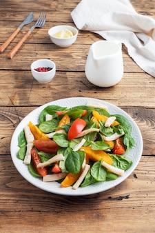イカの煮物、フレッシュトマト、ほうれん草の葉のサラダ。野菜とシーフードが入ったおいしい明るいダイエット料理。