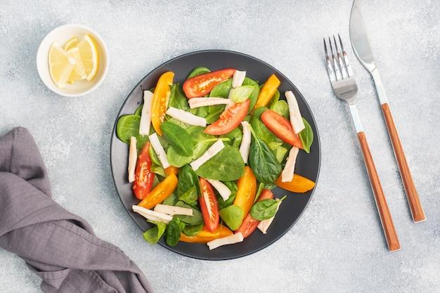 삶은 오징어, 신선한 토마토, 시금치 잎 샐러드. 야채와 해산물로 맛있는 밝은 다이어트 요리.