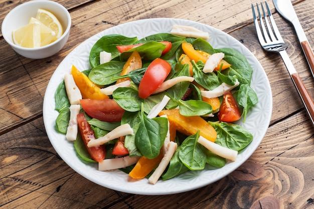 삶은 오징어 샐러드, 신선한 토마토, 시금치 잎. 야채와 해산물을 곁들인 맛있는 밝은 다이어트 요리.