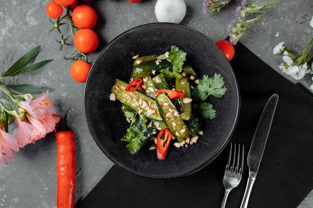 Салат из битых огурцов с кунжутом, сахаром, красным и черным перцем, оливковым маслом.