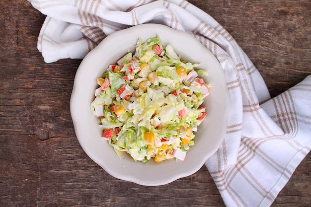 Салат из капусты с зернами кукурузы и крабовыми палочками в тарелке на старом фоне вид сверху