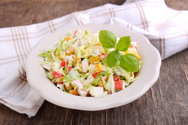Салат из капусты с зернами кукурузы и крабовыми палочками в тарелке на старом фоне