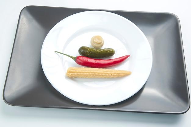 キノコの缶詰と漬物のサラダ、きゅうり、赤唐辛子の白い皿に