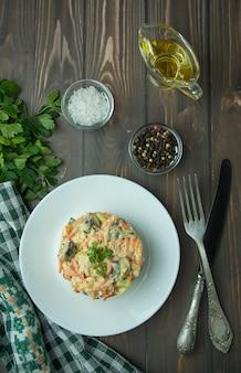 マヨネーズで味付けしたニンジン、鶏肉、ゆで卵のサラダ。白い皿に鶏肉と野菜のサラダの側面図です。暗い背景の木。表の背景メニュー。夕食のテーブル。