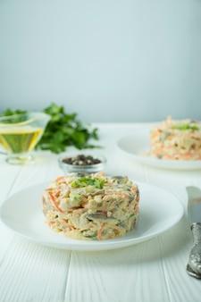にんじん、鶏肉、ゆで卵のマヨネーズ風味のサラダ。白い皿に鶏肉と野菜のサラダの側面図です。軽い木製の背景。テーブル背景メニュー。夕食のテーブル。