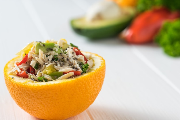 白いテーブルの上にオレンジ色のチキン、アボカド、ピーマン、ハーブのサラダ。トロピカルフルーツとチキンのダイエット食品。