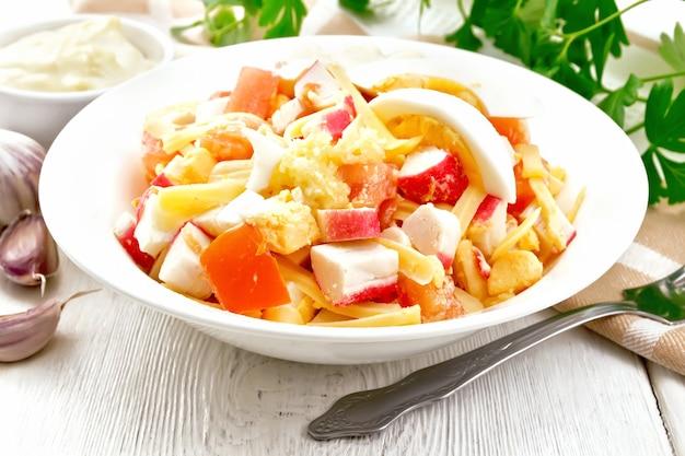 カニカマ、チーズ、ニンニク、トマト、卵のサラダとマヨネーズのプレート、タオル、パセリ、フォークを明るい木の板の背景に