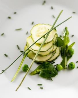 Салат из огурцов на белой тарелке крупным планом