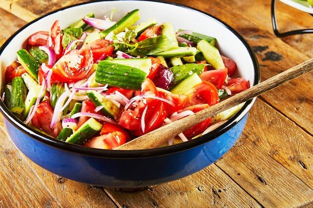 きゅうり、トマト、玉ねぎ、ハーブのサラダを木製のテーブルの青白のボウルに入れます。