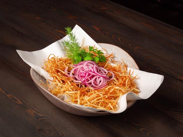 나무 버려진 보드의 배경에 그릇에 감자 튀김, 붉은 양파와 신선한 야채 샐러드
