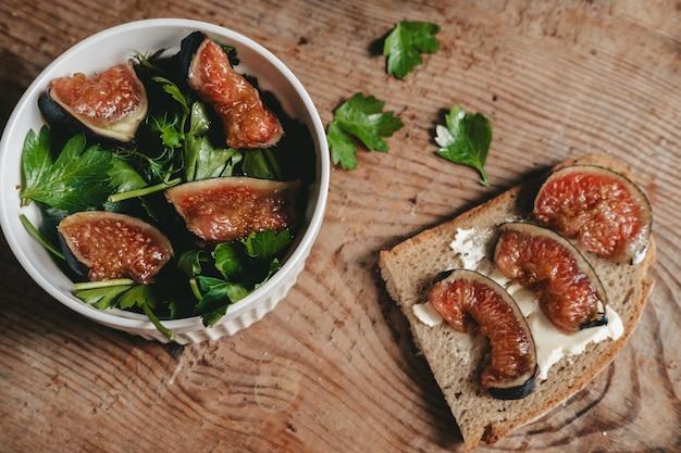 木製の背景に白いボウルに新鮮なイチジクとハーブのサラダ。チーズとイチジクで乾杯。ヘルシーなグリーンサラダと新鮮な果物と野菜のスナック。