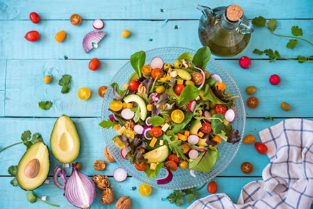 신선한 유기농 야채 샐러드와 파란색 배경에 엑스트라 버진 올리브 오일 한 병