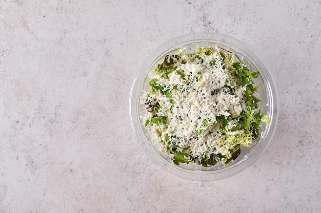 Салат из свежих овощей с сыром в прозрачном пластиковом контейнере.