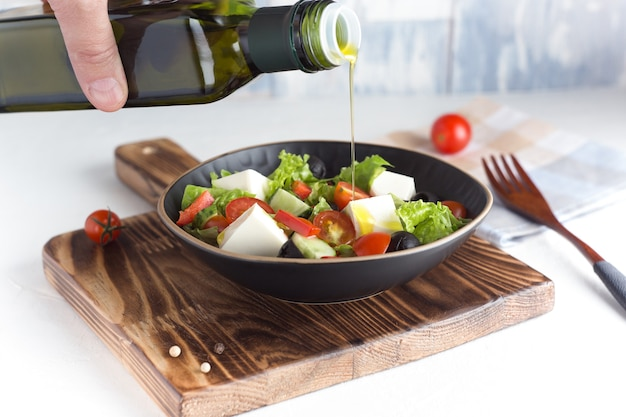 白い背景の上のギリシャ風サラダのボトルから注ぐオリーブオイルと新鮮な野菜のサラダ