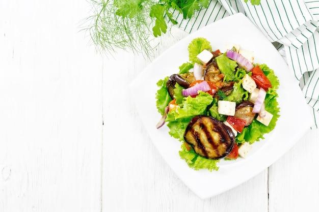 揚げ茄子のサラダ、玉ねぎと塩味のフェタチーズのトマト、プレートのレタスに植物油と醤油で味付け、上から明るい木の板の背景にナプキン