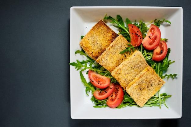 揚げ豆腐のトマトとロキュラのサラダ。黒の背景に白いプレートで自家製野菜サラダ。健康的なアジアの食事ビーガンベジタリアンサラダ。