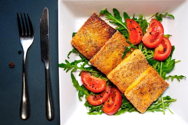 토마토와 로큘라를 곁들인 튀긴 두부 샐러드. 검정색 배경에 흰색 접시에 수제 채식 샐러드. 건강한 아시아 다이어트 채식주의자 샐러드입니다.