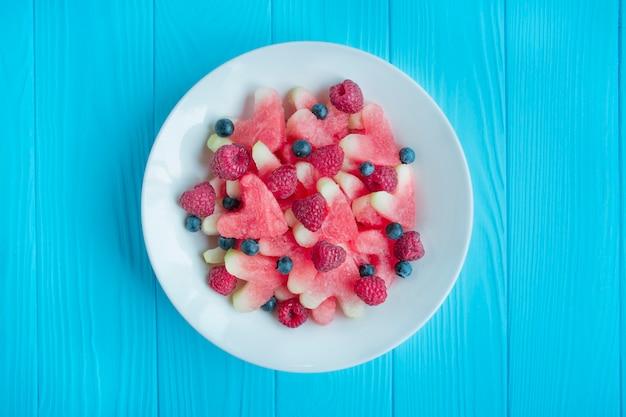 フルーツとベリーのサラダ。軽いハート型のスイカのサラダ、ラズベリー、青い木製の背景の白いプレートにブルーベリー。ベジタリアン料理。夏の料理。健康食品のバランス。