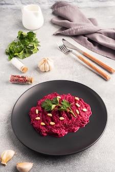 Салат из тертых кедровых орешков и петрушки со сливочным соусом на тарелке.