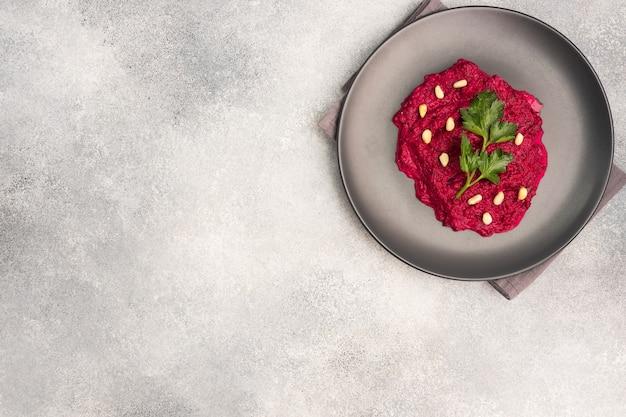 접시에 크림 소스를 곁들인 강판 비트 뿌리 잣과 파슬리 샐러드
