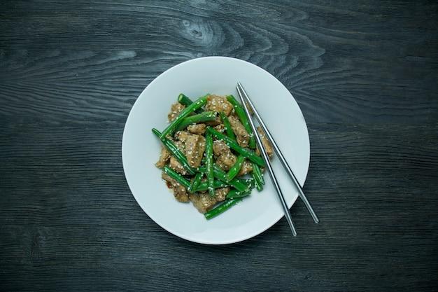ゴマをまぶしたインゲンと肉のサラダ。緑色の豆とホットサラダを提供しています。アスパラガスのサラダ。アジア料理。暗い背景の木。