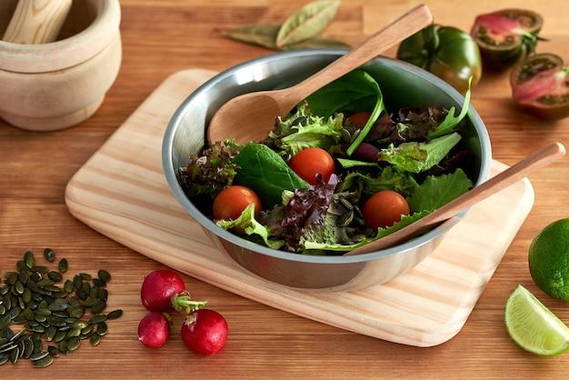 Салат из зеленых ростков, салата, шпината, помидоров черри, семян, редиса, лайма и лавровых листьев, подается в металлической миске на деревянной разделочной доске на кухонном столе ресторана рядом с деревянной ступкой.