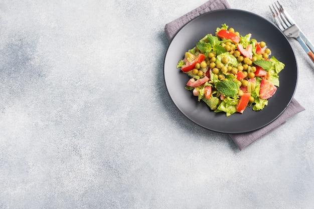 黒いプレートにソースで味付けしたグリーントマトの葉とエンドウ豆の缶詰のサラダ。春のフレッシュダイエットサラダ。上面図のコピースペース。